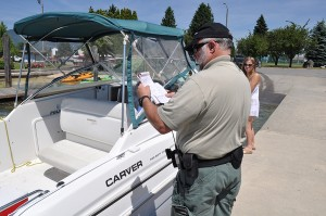 Sheriff's deputy Eric Ahrens conducts a boat inspection. Photo by Cameron Rasmusson