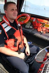 Brandon Hermenet at the helm of the Timberlake Fire Boat. Photo by Ben Olson.