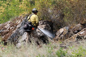 A firefighter sprays down a hot spot near the western slope of the fire line near Cape Horn in July, 2015. Photo by Ben Olson.
