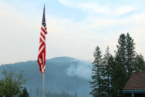 The American flag flies over the Bayview Community Center as smoke from the Cape Horn fire billows in the background. Photo by Ben Olson