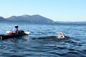 Roni Hibben swims with kayak support crew Randy Hixon. Photo by Ben Olson.