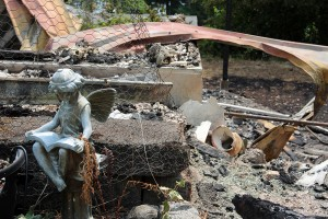 A piece of yard art remains after the home it once decorated is left in ashes. Photo by Ben Olson.