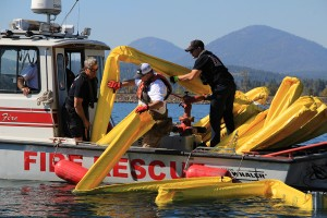 Boat crews deploy the boom floats to catch the oil spill. Photo by Ben Olson.