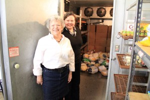Alice Wallace, left, and Debbie Love, right, stand before a walk-in freezer that holds donated turkeys. Photo by Ben Olson.