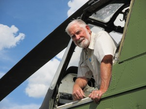 Vietnam veteran Bill Collier poses in his derelict H-34 helicopter, the same model he flew in the war – and the subject of his new book. Photo by Carla Keefer.