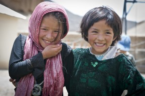 BAMYAN PROVINCE, Afghanistan - Two local girls enjoy the Arzu Studio Hope garden and playground in Dragon Valley, west of the town of Bamyan, June 20, 2012. Women enrolled the Arzu program receive higher-than average compensation for their work as rug weavers, and are required to attend literacy classes. They also have access to day care for their children, hot water to wash clothes, a kitchen, and a garden where they can grow their own vegetables and herbs. Younger children attend classes before and after weaving the rugs. (U.S. Army photo by Sgt. Ken Scar, 7th Mobile Public Affairs Detachment)