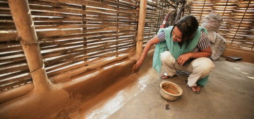 A woman coats her wall in dung to keep insects out at a Bhutanese refugee camp.