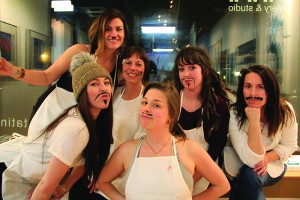 The group of Syringa Salon hairdressers and Cadie show off their acrylic mustaches. Photo by Ben Olson.