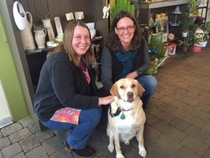 Kim Helms, left, and Petal Talk owner Nicole French, right, pose with Drake.