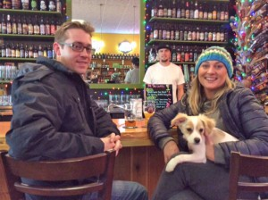 Customers John Grubbs and Lindsay Nance pose with their new pooch Reggie, while Jake Hagadone looks on from behind the bar.