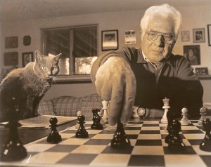 Lou Domanski at the chess board, with a furry apprentice looking on. Courtesy photo.