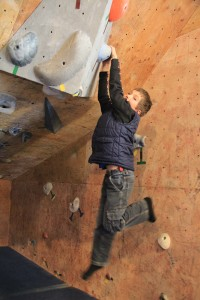 Micah Stoneham, 8, hangs from a wall at Sandpoint Rock Gym. Photo by Ben Olson.
