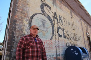 """Owner John Ford stands in front of the historic """"ghost sign"""" for Sandpoint Cleaners, which operated from 1945-1960. Photo by Ben Olson."""