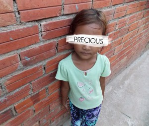 A young girl saved from human trafficking poses against a brick wall. Photo courtesy of Rapha House.