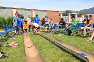 Nathan Ford (crouching behind car) launches his solar car during Tuesday's competition at SMS. Photo by Ben Olson.
