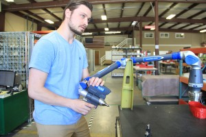 Tamarack employee Eric Schneider takes a 3D scan of a faro arm at the Ontario Street facility. Photo by Ben Olson.