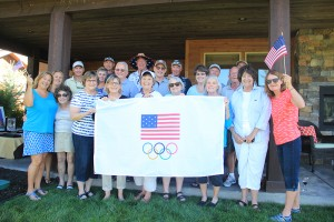 Karen Burnett, middle behind banner with white hat, stands with friends and neighbors in front of a banner they all plan to sign. Karen will hand deliver the banner to Rio in support of the men's freestyle wrestling team. Photo by Ben Olson.
