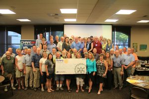 Rotarians, guests and sponsors proudly show off the $50k check donated to LPOSD. Photo by Ben Olson