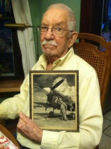 Howard Riggs holding a photo of him with a P-40. Courtesy photo.