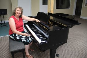Top: Karin Wedemeyer sits at the 1962 Yamaha G-2 grand piano recently donated to MCS. Photo by Ben Olson.