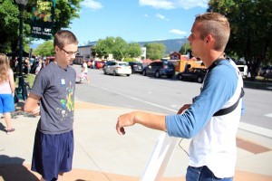 Chris Hutto, right, preaches to a Sandpoint youth at the Farmers' Market in Sandpoint. Photo by Ben Olson.