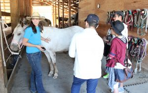 Wrangler Danielle Otis, left, shows exchange students around Western Pleasure Guest Ranch. Photo by Landon Otis.