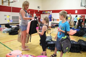 A mother and her two children pick out new backpacks at Farmin-Stidwell Elementary School on Tuesday. Photo by Ben Olson.