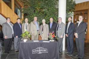 From left to right: Kelly Prior, Brent Carr, Cary Kelly, Jim Frank, Todd Sudick, Dan Hoffman, Glen Bailey, Ben VanGerpen and William Wilson meet Tuesday to sign the tax deferment agreement for the facility expansion. Photo by Cameron Barnes