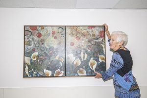"Polly Mire adjusting a painting called ""Tranquility"" by Catherine Earle at Bonner General Health. Photo by Cameron Barnes."