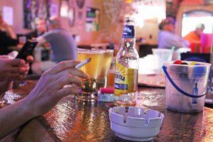 A patron at A&P's enjoys a cigarette inside the bar. Photo by Ben Olson.