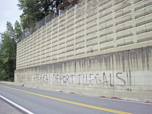 The graffiti in question, sprayed on the retaining wall of the historic Chinese cemetery in Hope. Photo by Sandy Compton.