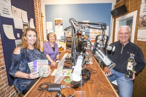 From Left to Right: Jennifer Berkey (Auction Organizer), Suzy Perez (Station Manager) and Charlie Parrish (President of the Board) hold up a few of the tangible items up for auction in the KRFY 88.5 Panhandle Community Radio Station on First Avenue. Photo by Cameron Barnes