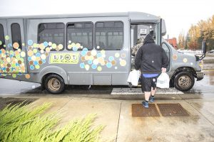 A rider boards the SPOT bus in the blowing rain on Wednesday afternoon in Sandpoint. Photo by Cameron Barnes.