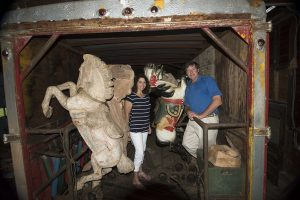 "Reno and Clay Hutchison stand amidst the hand-carved horses in one of two vintage trailers containing the 1920 ""Carousel of Smiles"" to be unloaded Dec. 3. Courtesy photo."