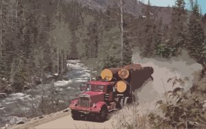In this vintage photo by Bill Hawkins, a logging truck drives down a mountain road in North Idaho.