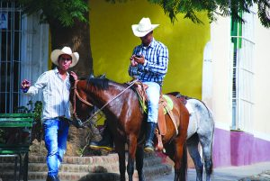 In Trinidad, Cuba, cowboys pause in a rare wifi zone to check the internet. Photo by Katie Botkin.