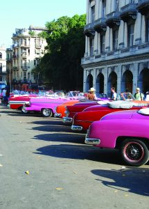 A rainbow of antique cars used as taxis line up in Havana near the capitol building.
