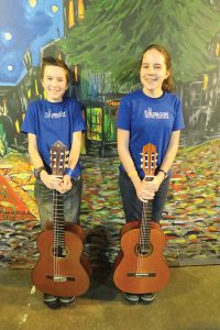 Israel Yandt, left, and Isabella Yandt, right, pose with their guitars after a lesson. Photo by Ben Olson.