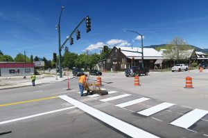 City workers paint new crosswalk stripes and traffic lanes at the intersection between Fifth Ave. and Cedar St. on Monday. Traffic will revert to two-way on Fifth Ave. on Thursday morning. Photo by Ben Olson.
