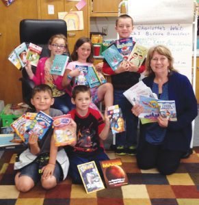 Ms. Davis and her second grade students at Farmin Stidwell excitedly show off their own monthly Book Trust books.  Front row from left to right: Toby Walker, Daniel Rodrigues, Ms. Davis,  Back row:  Jade Thompson, Hope Kelly, Jacob Alexander. Photo by Jim Ramsey.