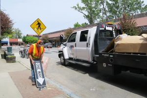 A road crew member takes down the one-way signs in downtown Sandpoint. Photo by Ben Olson.