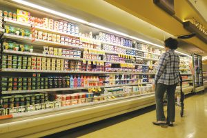 A shopper navigates the dairy section inside Sandpoint's Safeway grocery store. Photo by Ben Olson.
